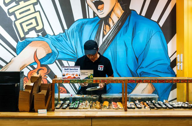 Woman making sushi in front of a cartoon sushi mural.