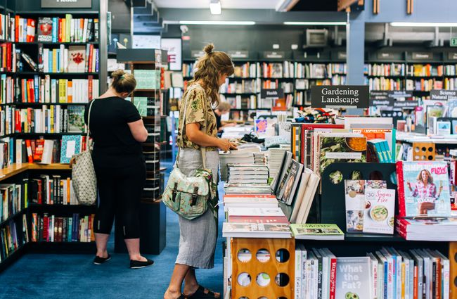A woman browsing books at the University of Canterbury Bookshop.