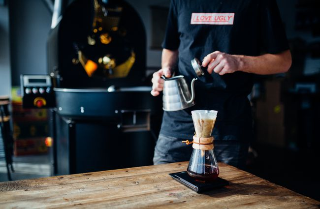 A barista making a Chemex coffee.
