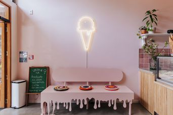 Ice cream light on a pink wall with a bench seat.