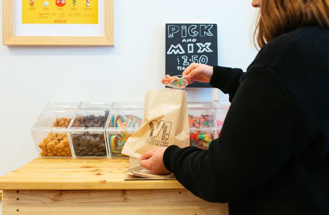 A woman serving up pick and mix.