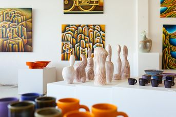 Sculptures on a white table, in front of artwork on the wall.