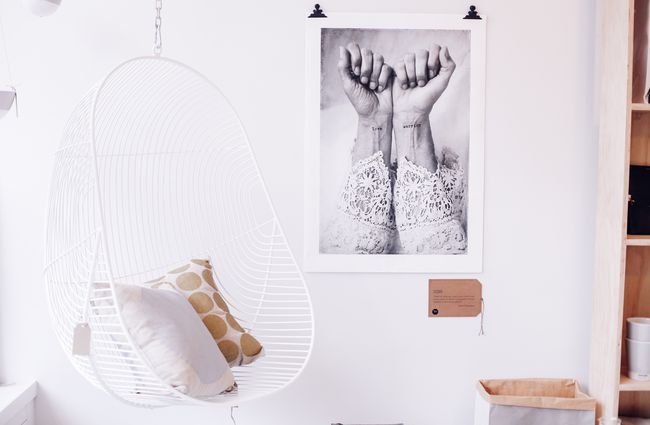 White hanging chair next to a black and white print.