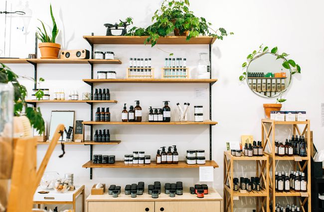 Beauty products and soaps on display on wooden shelves.
