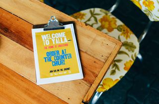 Welcome to Yalla menu on wooden table.